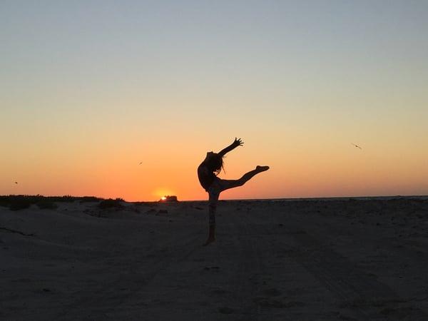femme sur une plage au coucher du soleil
